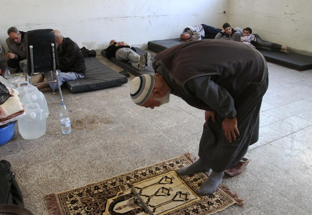 A Palestinian man who fled the Yarmuk Palestinian refugee camp prays inside a school in Damascus on April 6, 2015 (AFP Photo/Youssef Karwashan)