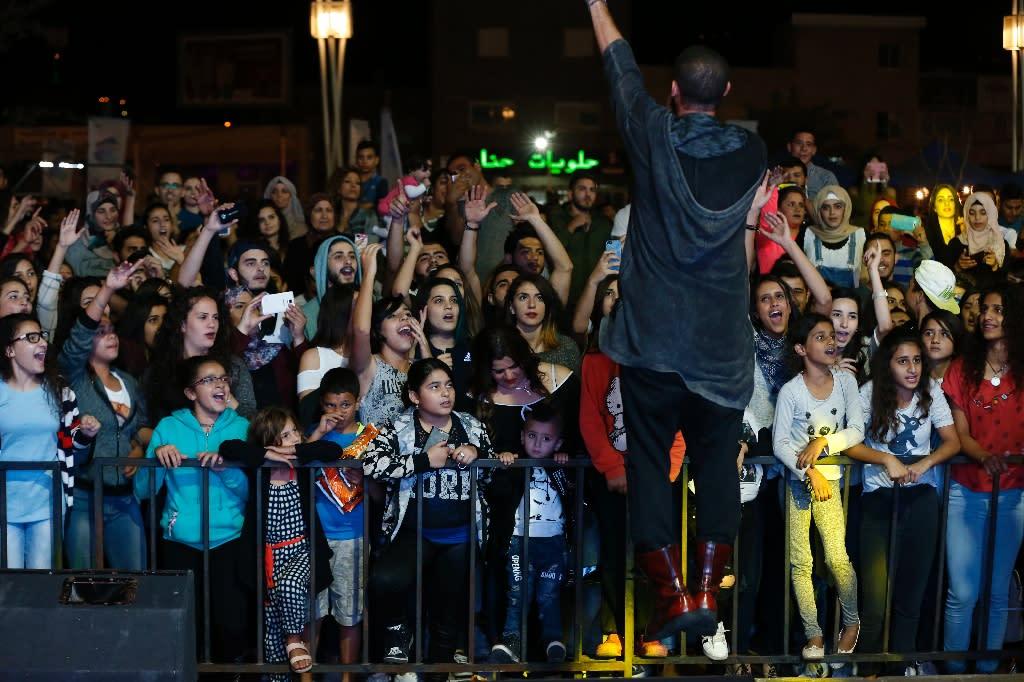 Audience members cheer as Arab-Israeli rapper Tamer Nafar performs on-stage during a festival in the northern Arab-Israeli town of Sakhnin (AFP Photo/Ahmad Gharabli)