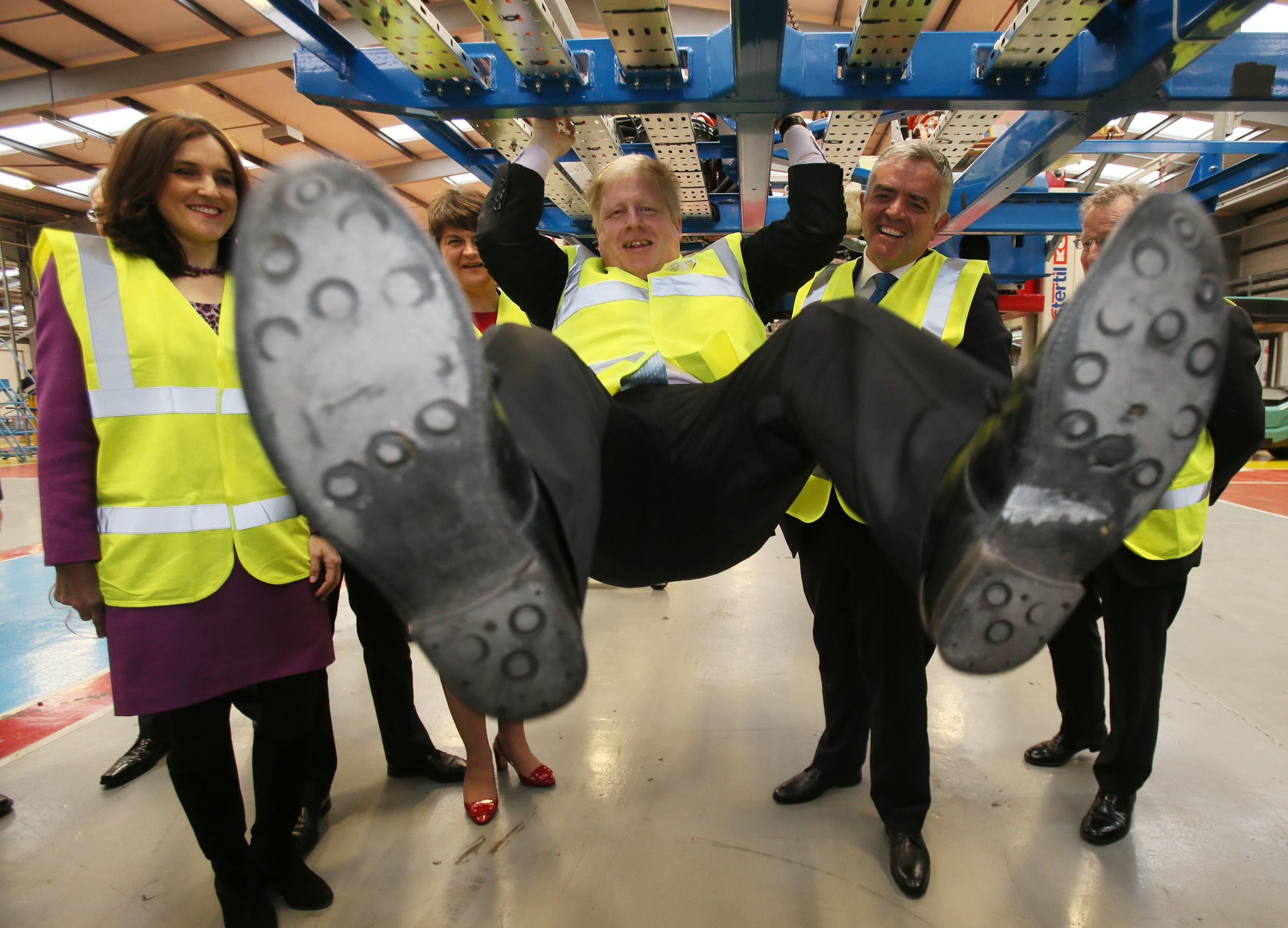 Mayor of London Boris Johnson (centre) swings from a bus as Northern Ireland Secretary Theresa Villiers (left), Northern First Minister and DUP leader Arlene Foster and Minister of Enterprise, Trade and Investment Jonathan Bell (second right) look on during a visit to Wrightbus Chassis plant in Antrim.
