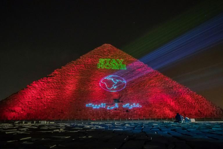 """At the Great pyramid of Kheops a laser projection spells out """"Stay home"""" (AFP Photo/Khaled DESOUKI)"""