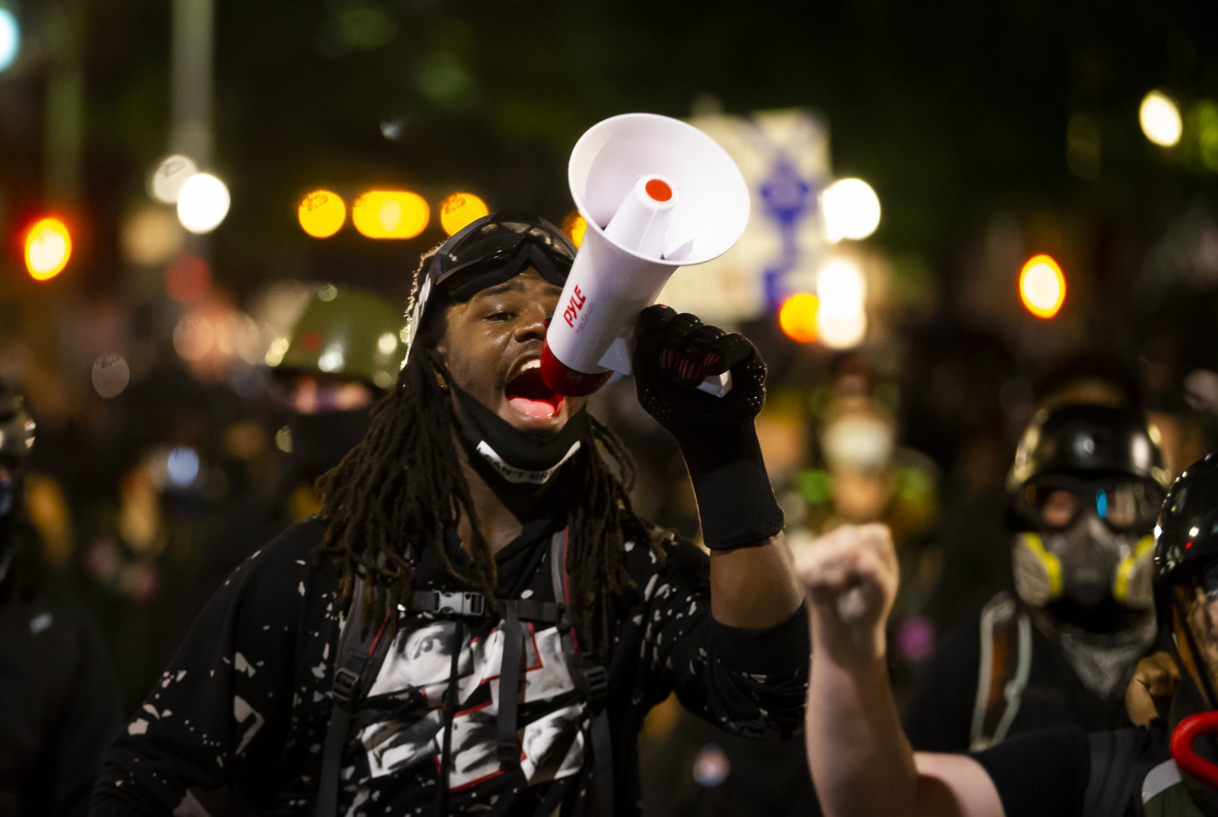 A protester uses a megaphone during a demonstration in Portland, Ore., on Tuesday, Aug. 25, 2020. Officials say protesters in Portland smashed windows at City Hall in a demonstration that started Tuesday night and stretched into Wednesday morning. (Dave Killen/The Oregonian via AP)
