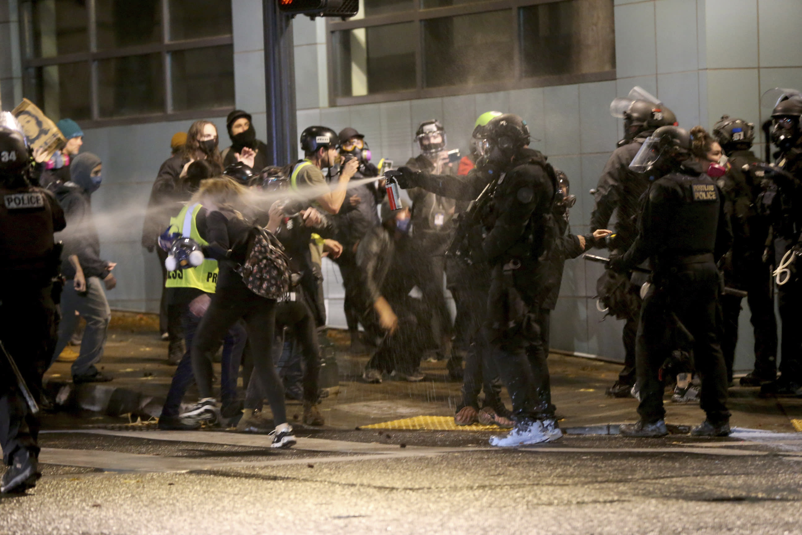 Protesters demanding the end of police violence against Black people are sprayed by police during a demonstration in Portland, Ore., on Wednesday, Sept. 23, 2020. Protesters in Portland hurled Molotov cocktails at officers in Oregon's largest city during a demonstration over a Kentucky grand jury's decision to not indict officers in the fatal shooting of Breonna Taylor, police said Thursday. (Mark Graves/The Oregonian via AP)