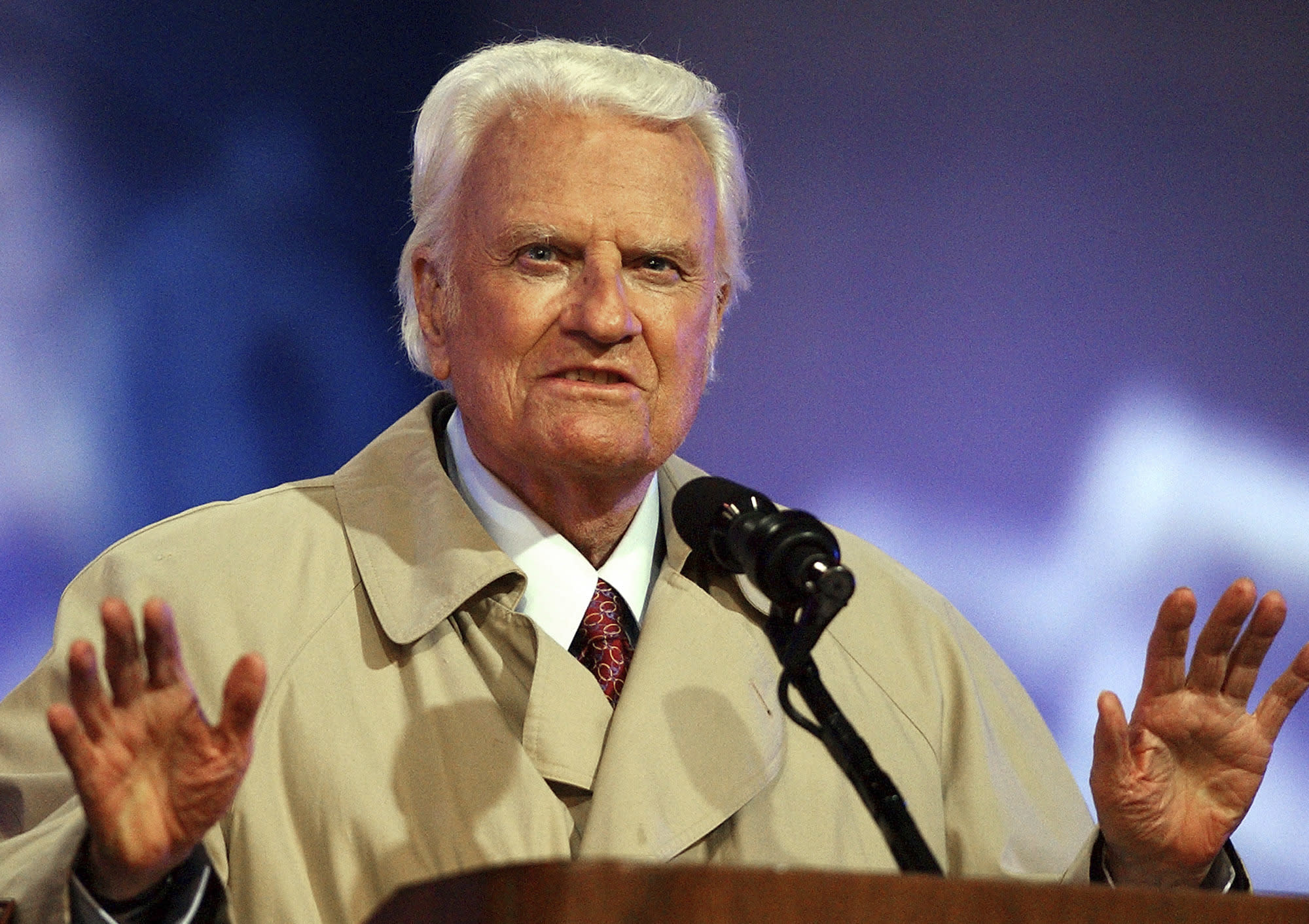 """FILE - In this May 9, 2003, file photo, the Rev. Billy Graham quiets the crowd during the second day of his Mission San Diego revival at Qualcomm Stadium in San Diego. President Donald Trump has visions of establishing by the final months of his second term—should he win one—a """"National Garden of American Heroes"""" that will pay tribute to some of the prominent figures in the nation's history, including Rev. Graham, that he sees as the """"greatest Americans to ever live."""" The president unveiled his plan Friday, July 3, 2020, during his speech at Mount Rushmore National Memorial, S.D. (AP Photo/Denis Poroy, File)"""