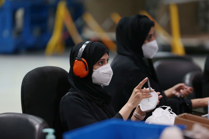Workers sort through N95 masks, made at the Strata Manufacturing facility, in Al Ain