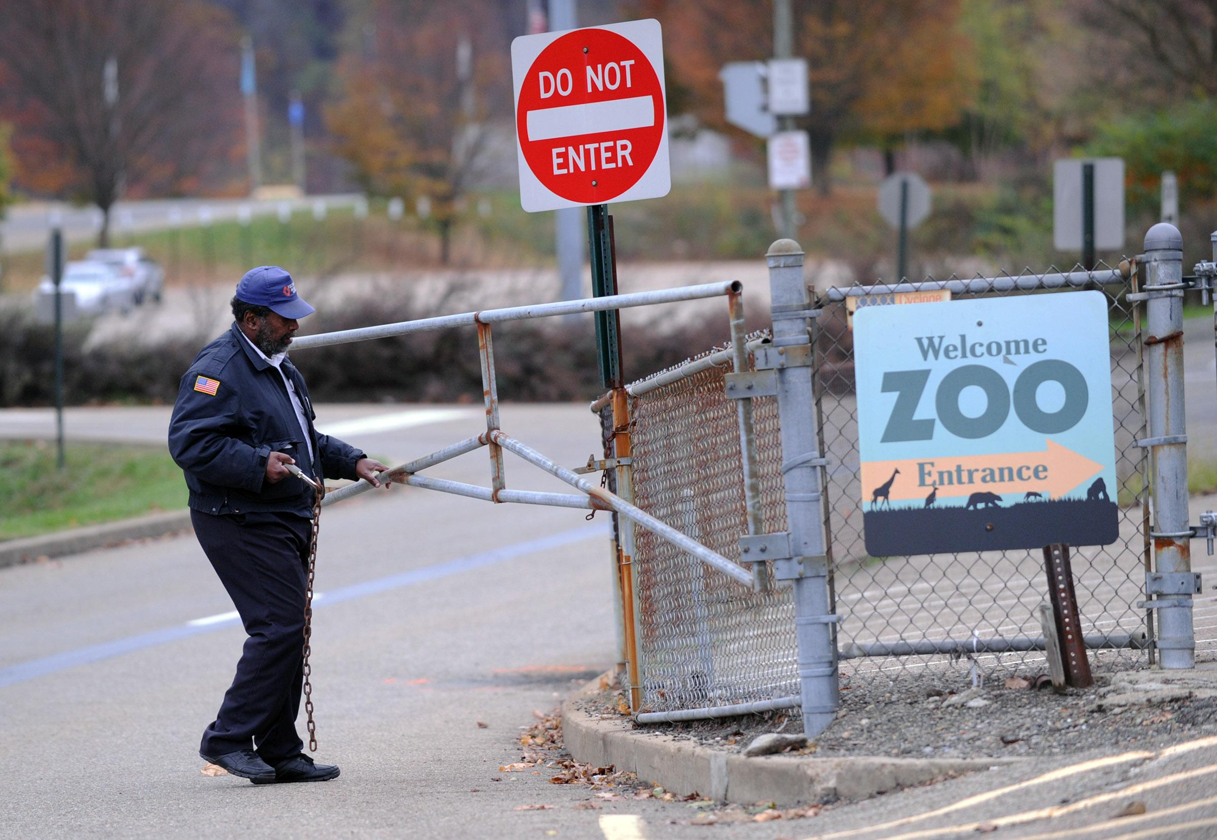 A security guard closes the gate at the Pittsburgh Zoo, where zoo officials say a young boy was killed after he fell into the exhibit that was home to a pack of African painted dogs, who pounced on the boy and mauled him, Sunday, Nov. 4, 2012. It's not clear whether he died from the fall or the attack, said Barbara Baker, president and CEO of the Pittsburgh Zoo & PPG Aquarium. (AP Photo/John Heller)