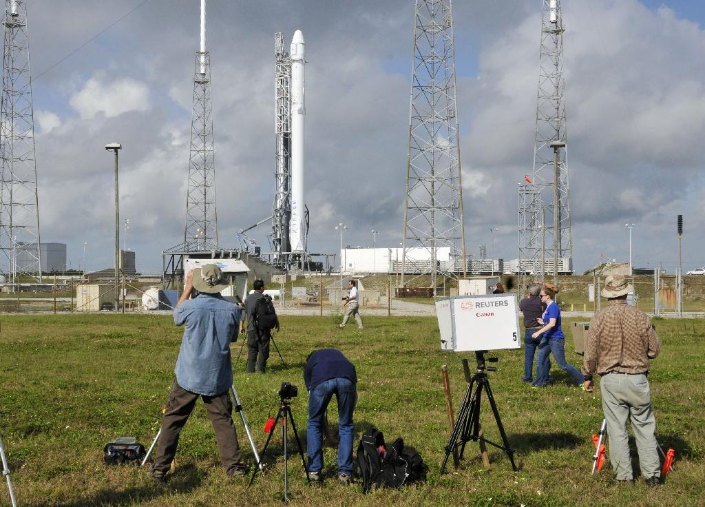 Photographers look on at the SpaceX Falcon 9 rocket, as they wait for the launch in Cape Canaveral, Florida on April 13, 2015 (AFP Photo/Bruce Weaver)