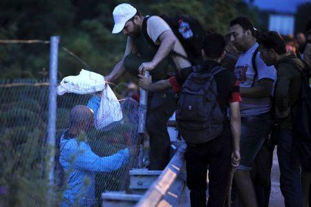 Immigrants from Syria cross a fence at Tabanovce near the Serbian border with Macedonia