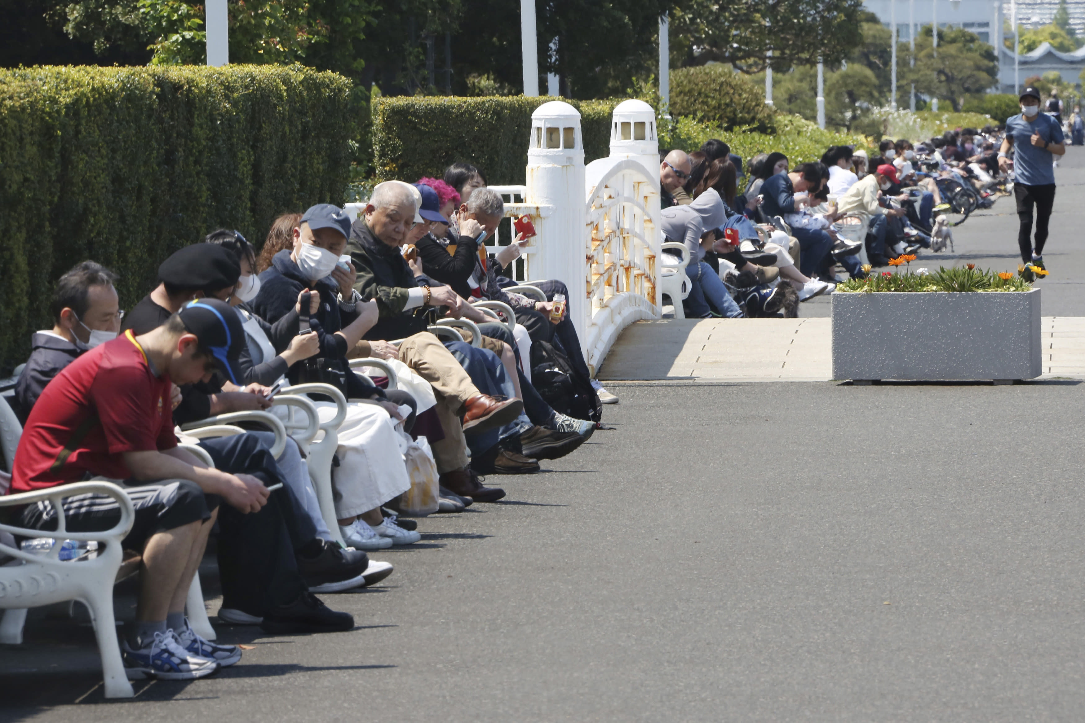 People sit on the bench at a park in Yokohama, near Tokyo, on a national holiday, Wednesday, April 29, 2020. (AP Photo/Koji Sasahara)