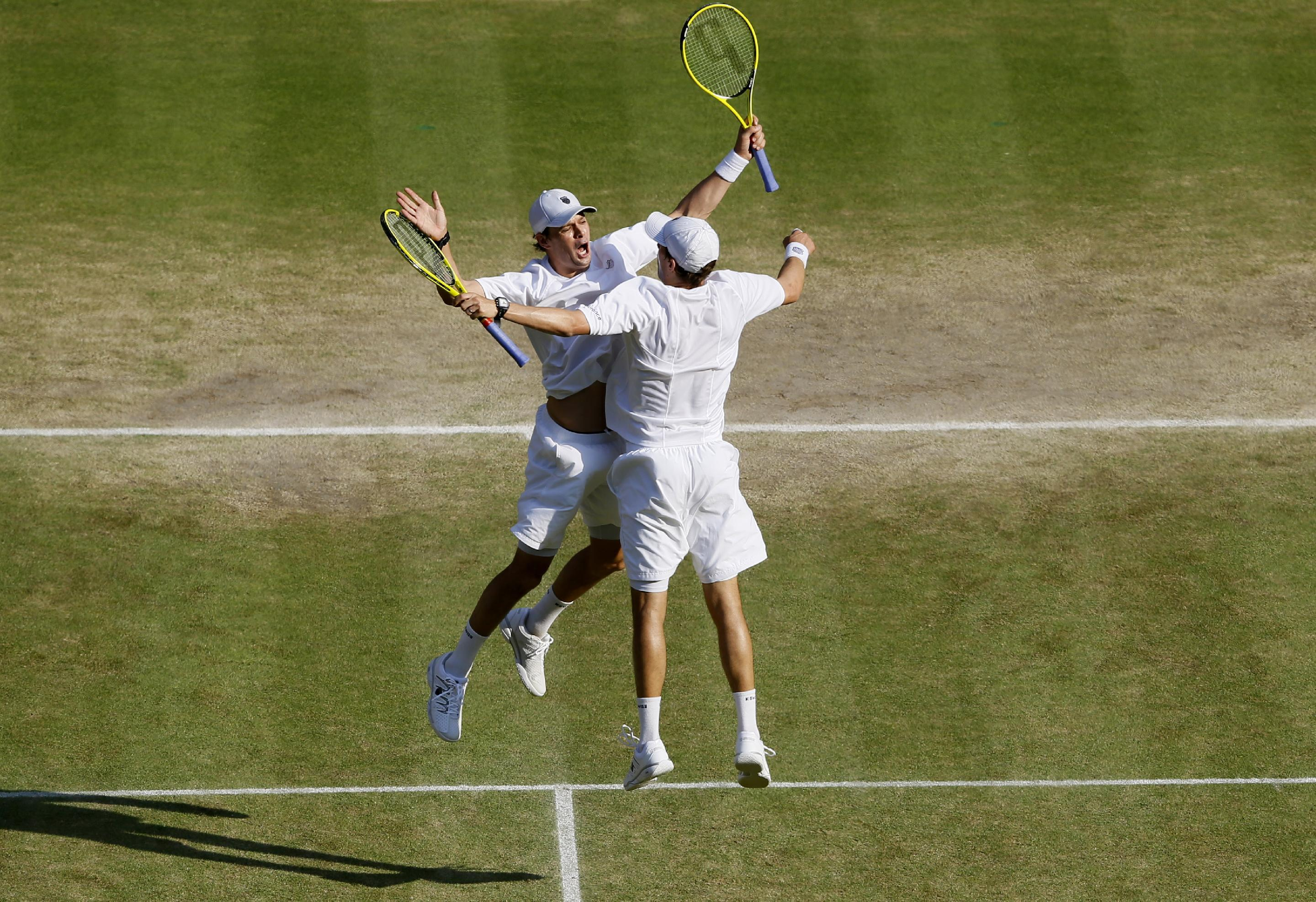 Bob Bryan and Mike Bryan of the United States celebrate after beating Ivan Dodig of Croatia and Marcelo Melo Brazil to win the Men's doubles final match at the All England Lawn Tennis Championships in Wimbledon, London, Saturday, July 6, 2013. (AP Photo/Kirsty Wigglesworth)