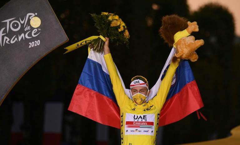 Slovenia's Tadej Pogacar wearing the overall leader's yellow jersey and draped in his national flag
