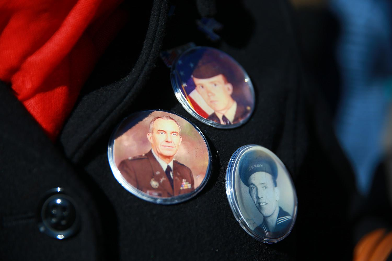 <p>A woman wears buttons of loved ones who served in the armed forces during the Veterans Day parade in New York on Nov. 11, 2018. (Photo: Gordon Donovan/Yahoo News) </p>