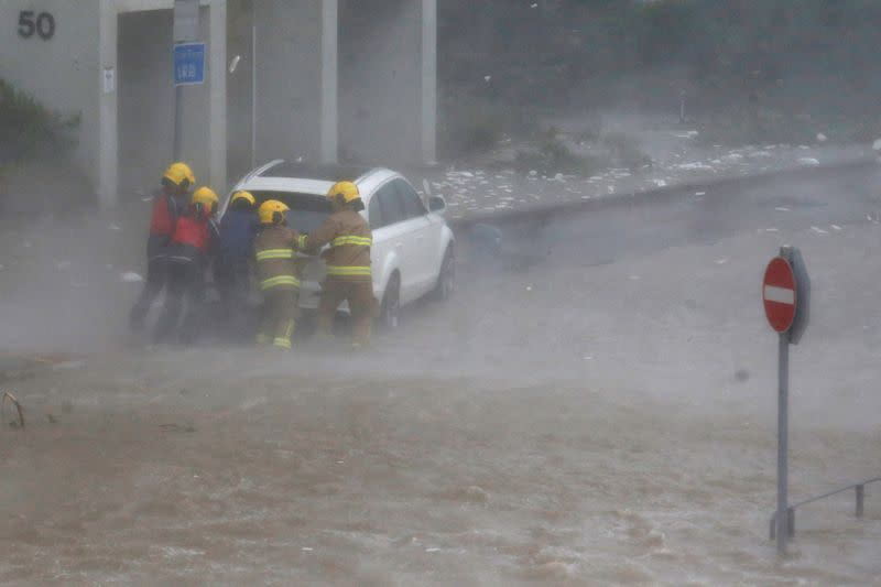 FILE PHOTO: Firefighters push a car in flooded waters as high waves hit the shore at Heng Fa Chuen, a residental district near the waterfront, as Typhoon Mangkhut slams Hong Kong