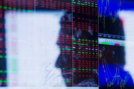 The face of a trader is reflected on the screen of a terminal on the floor of the New York Stock Exchange