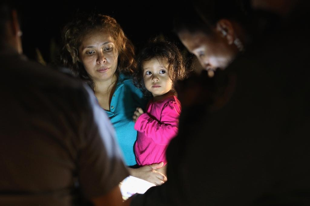 Central American asylum seekers, including a Honduran girl, 2, and her mother, near the US-Mexico border in McAllen, Texas (AFP Photo/John MOORE)