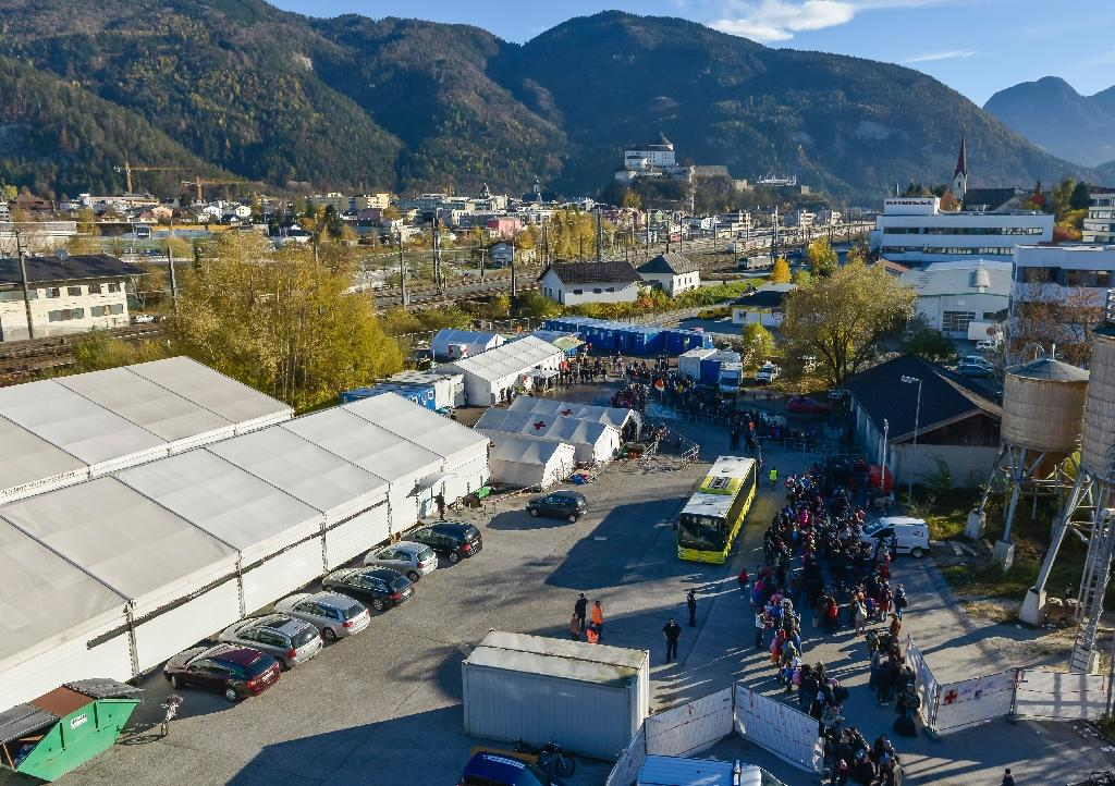 Migrants queue at a temporary shelter for refugees in the Austrian city of Kufstein, near the German border on November 3, 2015