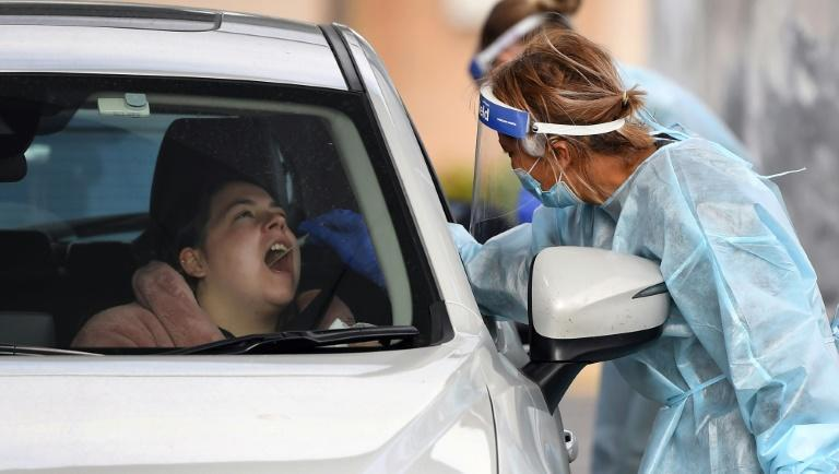 A coronavirus tester takes a swab sample at a drive-through testing station in Melbourne (AFP Photo/William WEST)