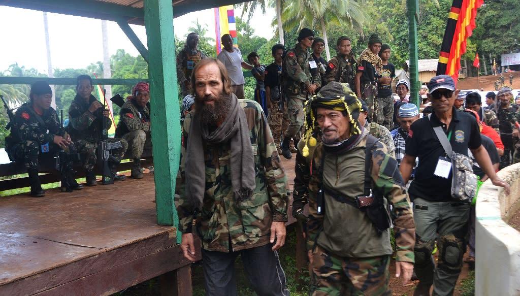 Moro National Liberation Front (MNLF) Chairman Nur Misuari (C right) escorts freed Norwegian Kjartan Sekkingstad (C left) at a handover ceremony in Indanan on September 18, 2016 (AFP Photo/Nickee Butlangan)