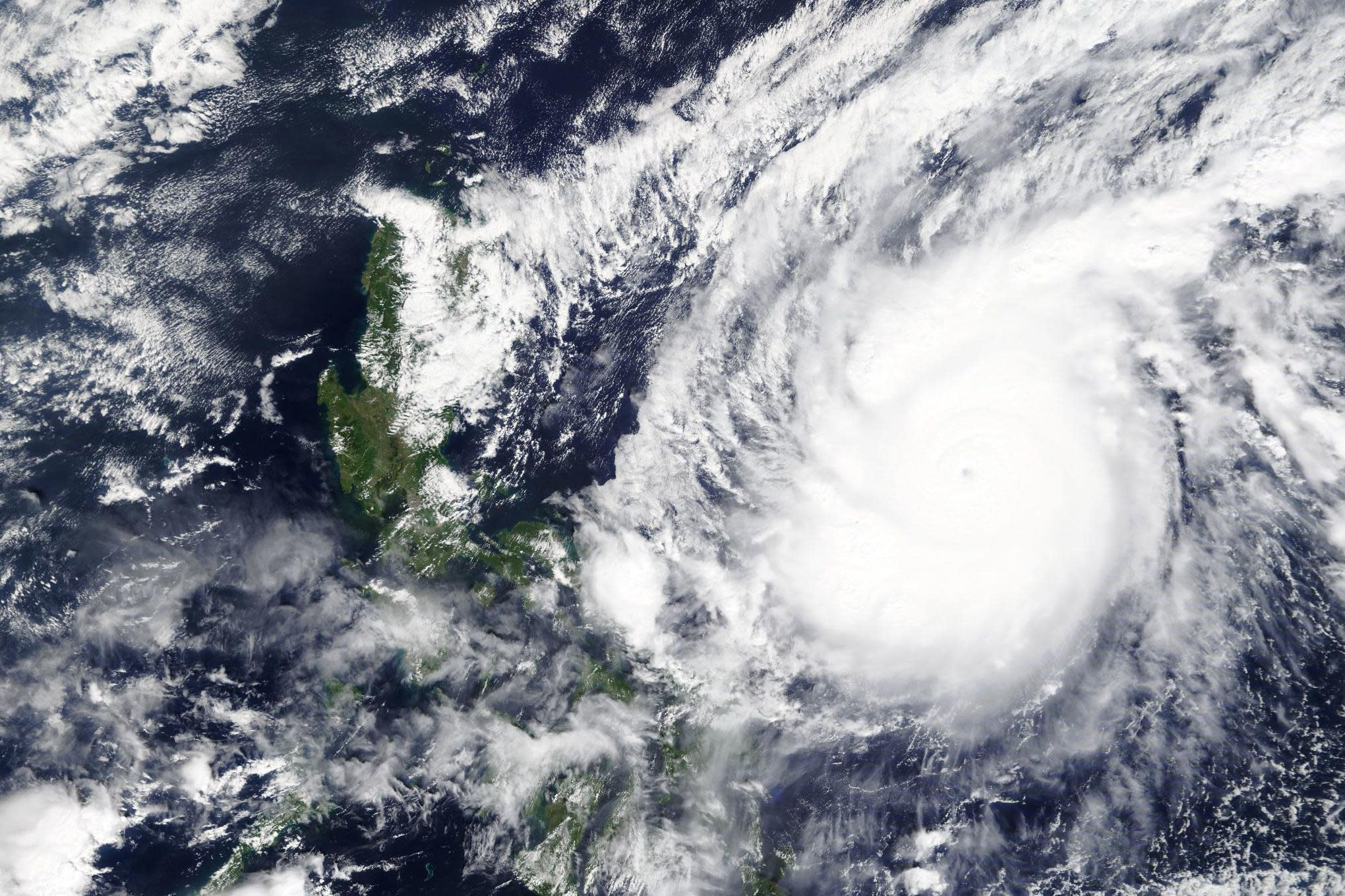 """This Saturday, Oct. 31, 2020, satellite image released by NASA Worldview, Earth Observing System Data and Information System (EOSDIS) shows a typhoon locally known as Goni moving around the Philippines. The super typhoon slammed into the eastern Philippines with """"catastrophic violent winds"""" early Sunday and about a million people have been evacuated in its projected path, including in the capital where the main international airport has been ordered closed, officials said. (NASA via AP)"""