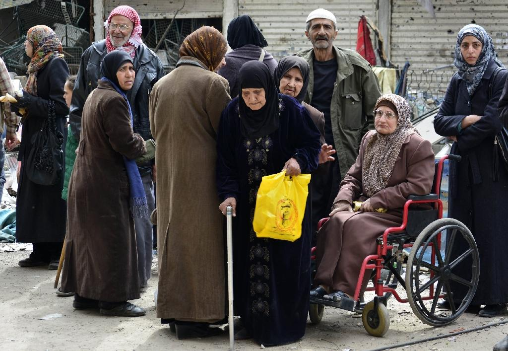 Palestinian refugees queue up to receive aid parcels from a local organisation at the besieged Yarmuk refugee camp, south of the Syrian capital Damascus, on March 11, 2015