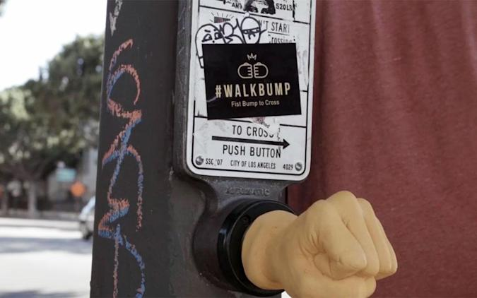 Fist-bumping a button is the best way to cross the street