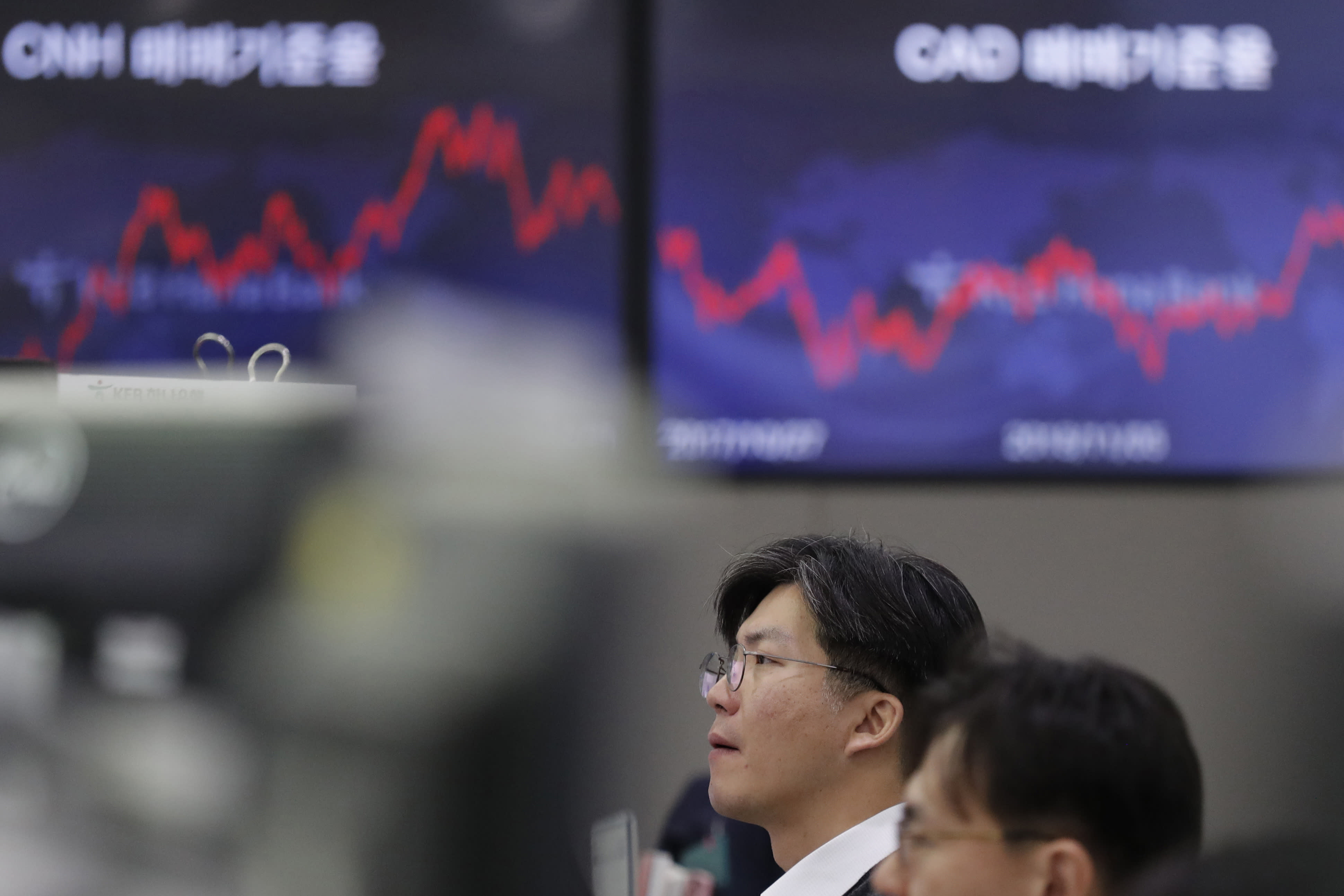 A currency trader watches computer monitors near the screens at the foreign exchange dealing room in Seoul, South Korea, Friday, Nov. 8, 2019. Asian stock markets were mixed Friday amid uncertainty about a possible U.S.-Chinese agreement to roll back tariffs in their trade war. (AP Photo/Lee Jin-man)
