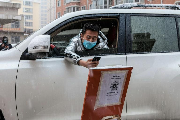 A driver scans a QR code to register information before entering a community in the border city of Suifenhe, in China's northeastern Heilongjiang province (AFP Photo/STR)