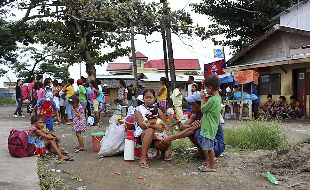 Residents wait to be transferred to an evacuation center in Tacloban city, central Philippines December 4, 2014. Schools and government offices were shut in parts of the central Philippines on Thursday and residents stocked up on supplies and food, as provinces yet to recover from last year's devastating super-typhoon Haiyan braced for another category 5 storm. Typhoon Hagupit was churning across the Pacific around 860 km (585 miles) east of the island nation on Thursday, the local weather bureau said, packing winds of up to 195 kph (120 mph) with gusts of up to 230 kph. REUTERS/Stringer (PHILIPPINES - Tags: POLITICS DISASTER)