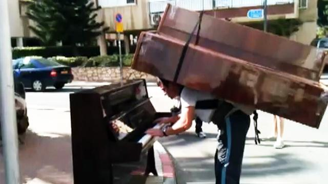Man plays piano with a piano on his back