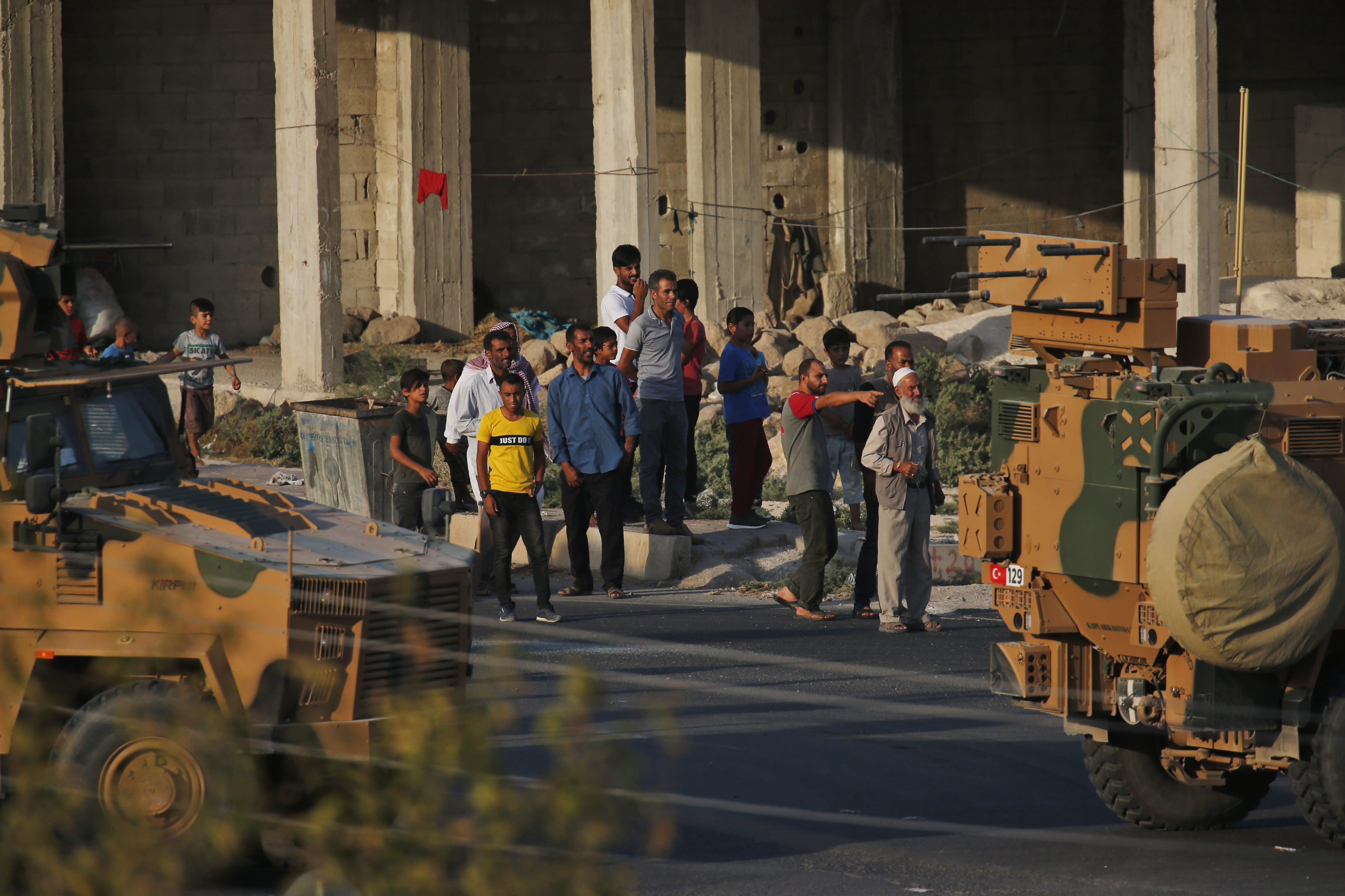 Shortly after the Turkish operation inside Syria had started, local residents cheer and applaud as a convoy of Turkish forces vehicles is driven through the town of Akcakale, Sanliurfa province, southeastern Turkey, at the border between Turkey and Syria, Wednesday, Oct. 9, 2019. Turkey launched a military operation Wednesday against Kurdish fighters in northeastern Syria after U.S. forces pulled back from the area, with a series of airstrikes hitting a town on Syria's northern border.(AP Photo/Lefteris Pitarakis)
