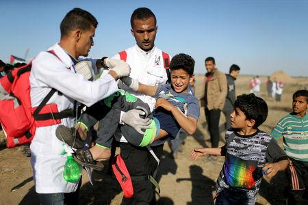 A wounded Palestinian boy is evacuated during a protest at the Israel-Gaza border fence, in the southern Gaza Strip May 3, 2019. REUTERS/Ibraheem Abu Mustafa