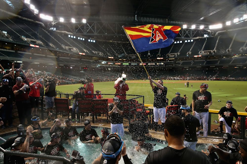 D-backs pitcher Archie Bradley waves an Arizona flag as the team celebrates in the outfield pool (Getty Images)