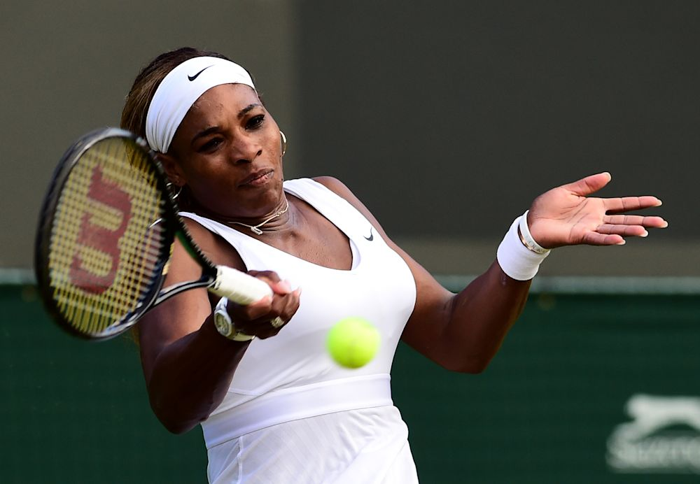 US player Serena Williams returns to France's Alize Cornet during their women's singles third round match on day six of the 2014 Wimbledon Championships at The All England Tennis Club in Wimbledon, southwest London, on June 28, 2014