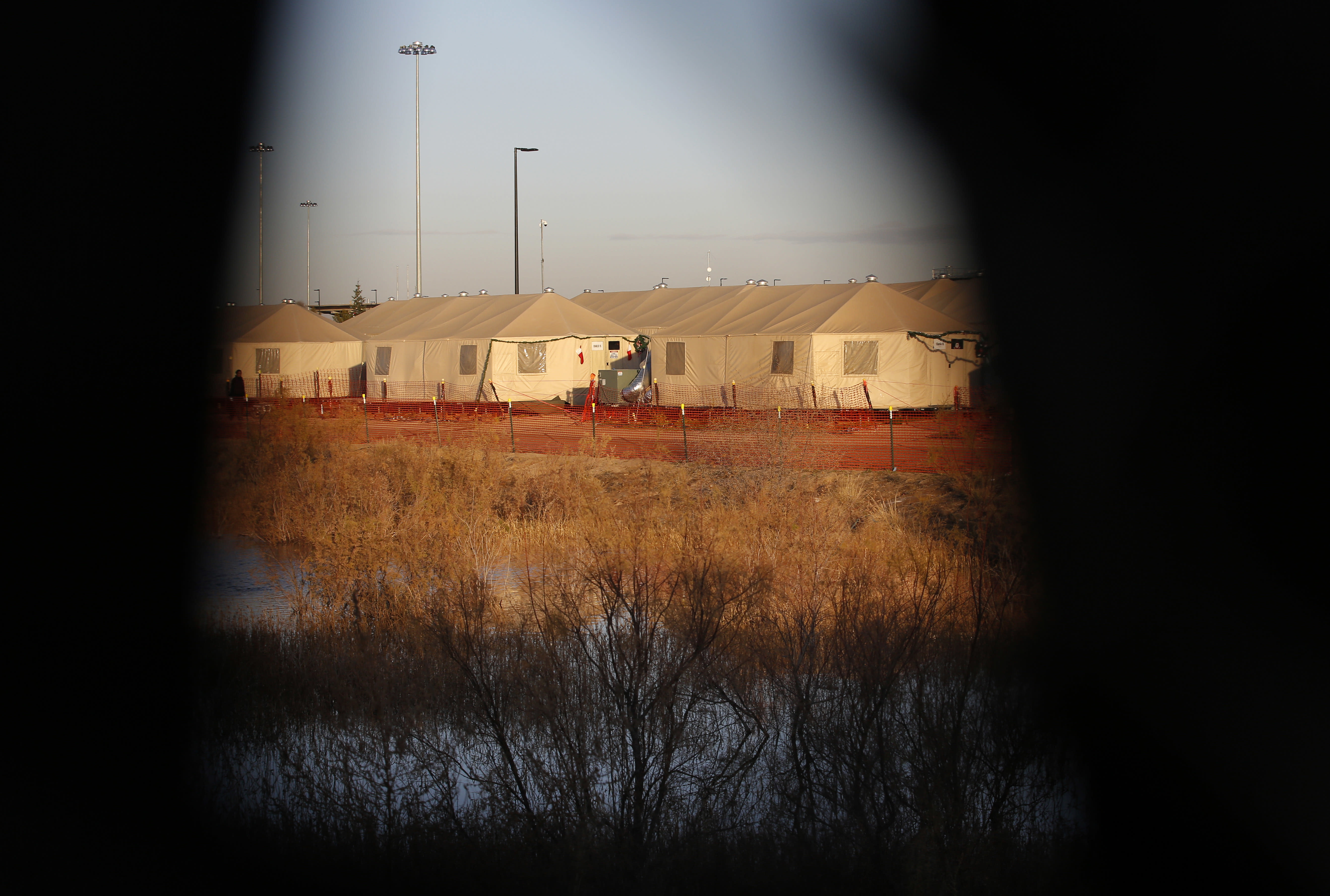 File-This Dec. 13, 2018, file photo shows tents through a hole in the tarp that covers the fence of the Tornillo detention camp for migrant teens in Tornillo, Texas. The nonprofit group running what was once the nation's largest detention camp for migrant children confirmed it is closing down the facility and the last kids left on Friday, Jan. 11, 2019. (AP Photo/Andres Leighton, File)