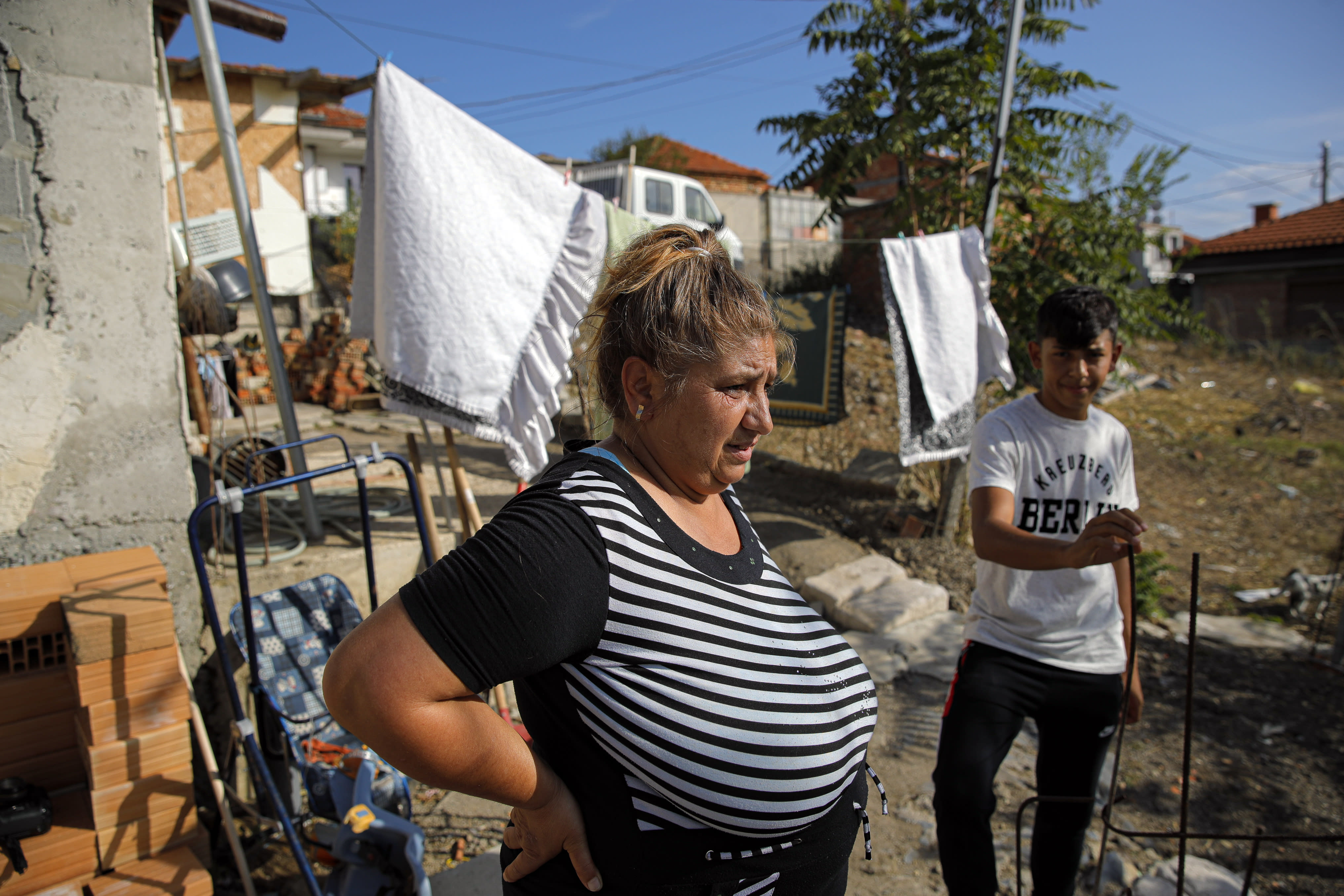 "Azime Ali Topchu, 48, a Bulgarian Roma woman, stands in her back yard in a village on the outskirts of Burgas, Bulgaria, Monday, Sept. 28, 2020. Human rights activists and experts say local officials in several countries with significant Roma populations have used the pandemic to unlawfully target the minority group, which is Europe's largest and has faced centuries of severe discrimination. Topchu said that the police-enforced lockdown of her village in Burgas, on Bulgaria's Black Sea Coast, made her family ""really sad."" (AP Photo/Vadim Ghirda)"
