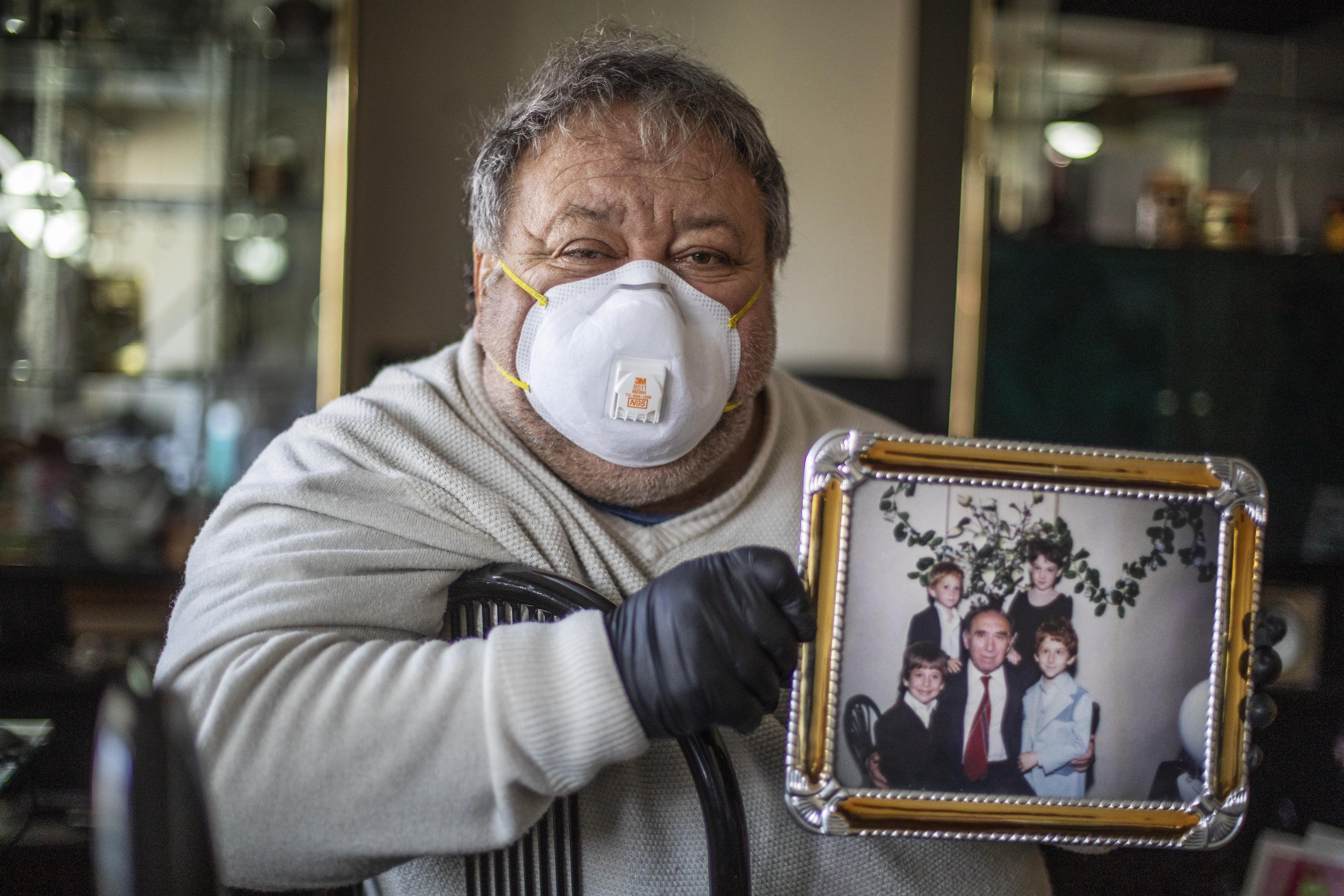 """Michael Tokar holds a picture of his father, David Tokar, as he cleans out his apartment after he died from complications caused by coronavirus, in the Brooklyn borough of New York, Sunday, April 12, 2020. """"He was born 92 years ago,"""" said Tokar, reciting a collection of facts that form a portrait. """"He collected stamps. He loved the racetrack. He adored his grandchildren."""" (AP Photo/David Goldman)"""