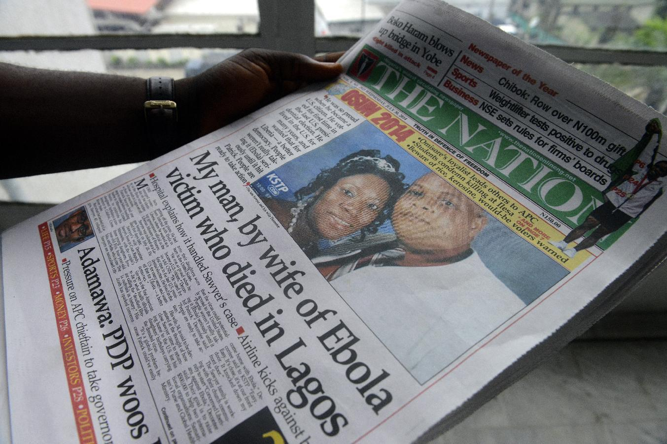 A man reads a newspaper featuring a front page story on the death of Liberian diplomat Patrick Sawyer (pictured with his wife Decontee) who died of the Ebloa virus in Lagos on July 30, 2014 (AFP Photo/Pius Utomi Ekpei)