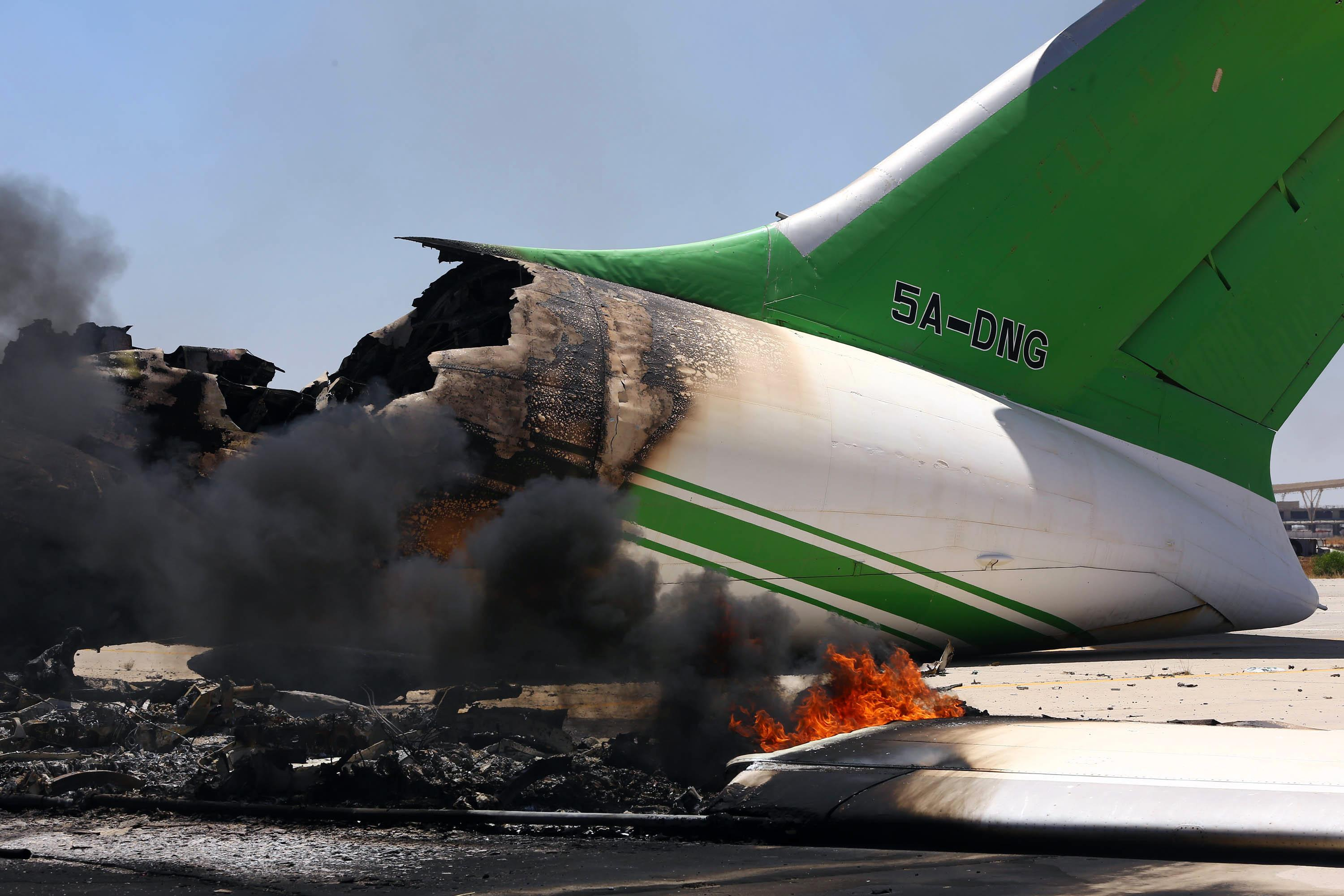 Flames and smoke billow from a plane that was destroyed during fierce clashes at Tripoli's international airport in the Libyan capital, on July 16, 2014 (AFP Photo/Mahmud Turkia)