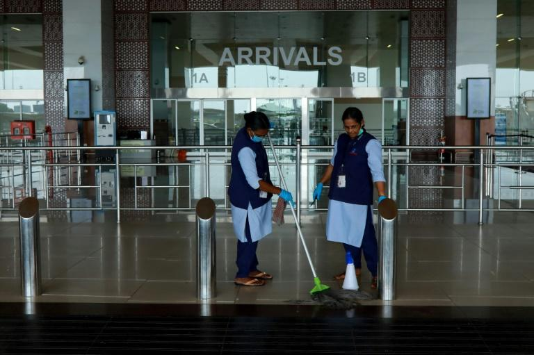 Staff clean the arrivals terminal at Cochin International Airport in Kochi ahead of the arrival of a first repatriation flight carrying Indian citizens from the Gulf (AFP Photo/Arunchandra BOSE)
