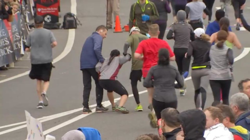 The woman is helped towards the finish line during the Philadelphia Love Run Half-Marathon