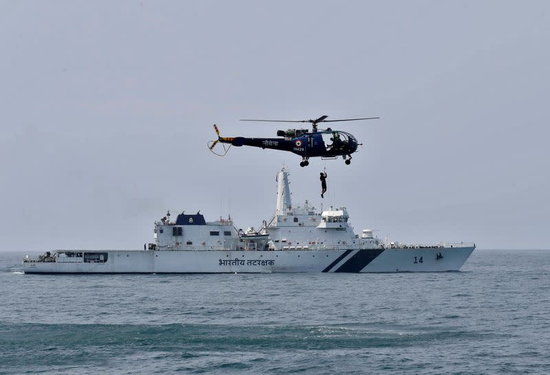 "FILE PHOTO: An Indian Navy ""Chetak"" helicopter demonstrates a rescue operation past the Coast Guard's Offshore Patrol Vessel (OPV) ""Sarathi"" during a media tour in the Arabian Sea near Kochi"