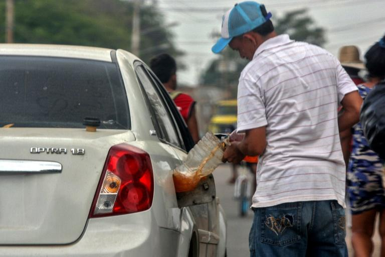 A man fills his car with gasoline purchased on the streets of Maracaibo, Venezuela in July 2020 (AFP Photo/Luis BRAVO)
