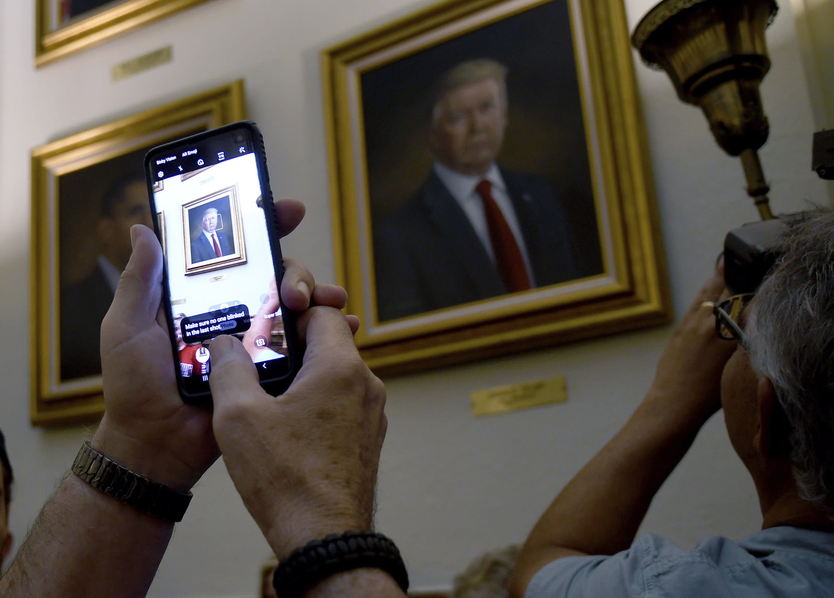 People take photos of President Donald Trump's portrait hanging in the Colorado Capitol after an unveiling ceremony Thursday, Aug. 1, 2019, in Denver. Colorado Republicans raised more than $10,000 through a GoFundMe account to commission the portrait, which was painted by Sarah Boardman, an artist who also produced the Capitol's portrait of President Barack Obama. (AP Photo/Thomas Peipert)