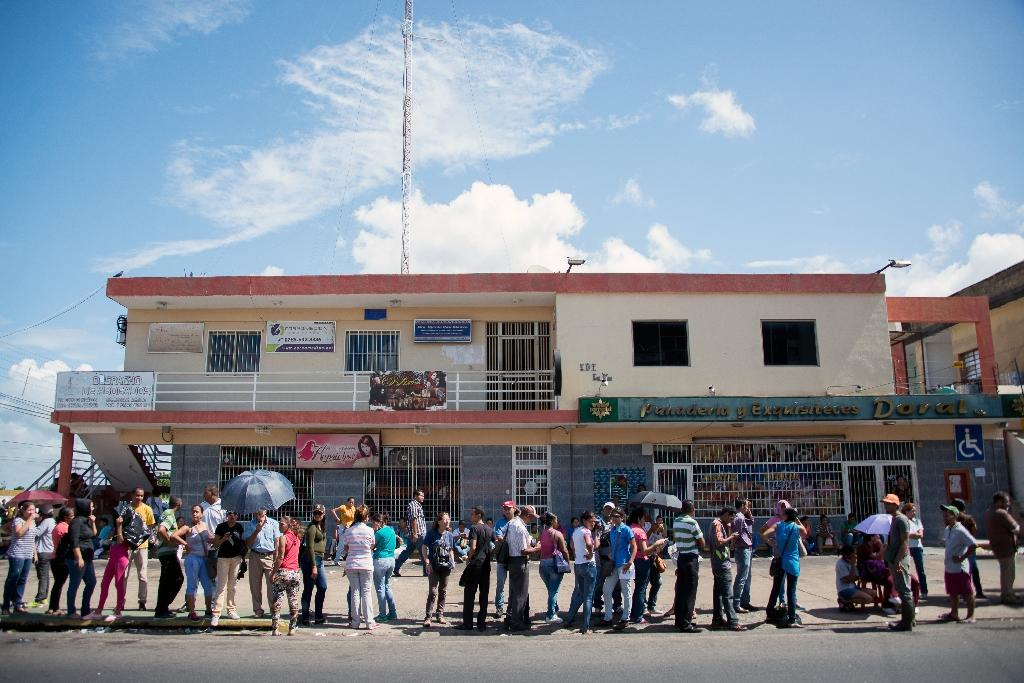 People queue outside a supermarket to buy basic food and household items in Ciudad Bolivar, Venezuela, on December 19, 2016 (AFP Photo/MANAURE QUINTERO)