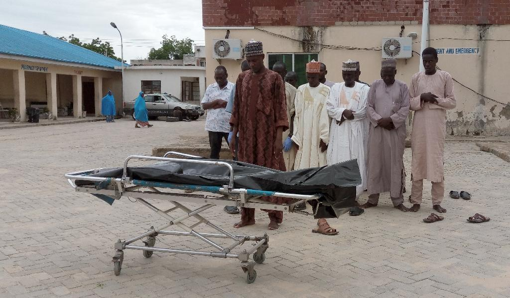 People pray over the body of a victim in the grounds of the State Specialist Hospital in Maiduguri, northeastern Nigeria on July 29, 2017 (AFP Photo/STRINGER)