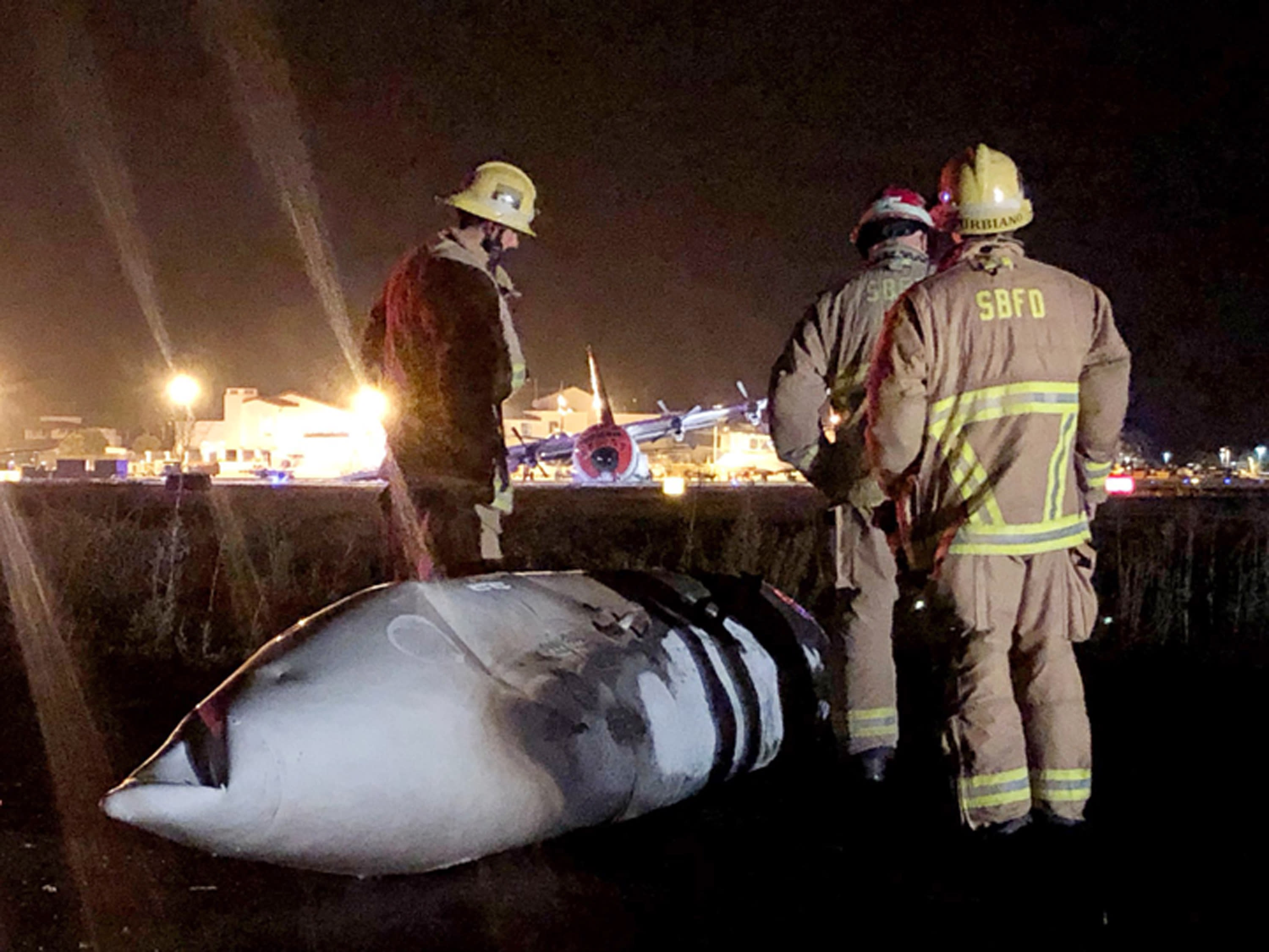 This Sunday, Aug. 25, 2019 photo provided by the Santa Barbara County Fire Department shows the wreckage of a Lockheed C-130 cargo pane after it crashed and burned at the Santa Barbara, Calif., Airport. Authorities say seven people escaped unhurt. The Federal Aviation Administration says the plane experienced hydraulic problems and crash-landed on its belly along a runway. (Mike Eliason/Santa Barbara County Fire Department via AP)