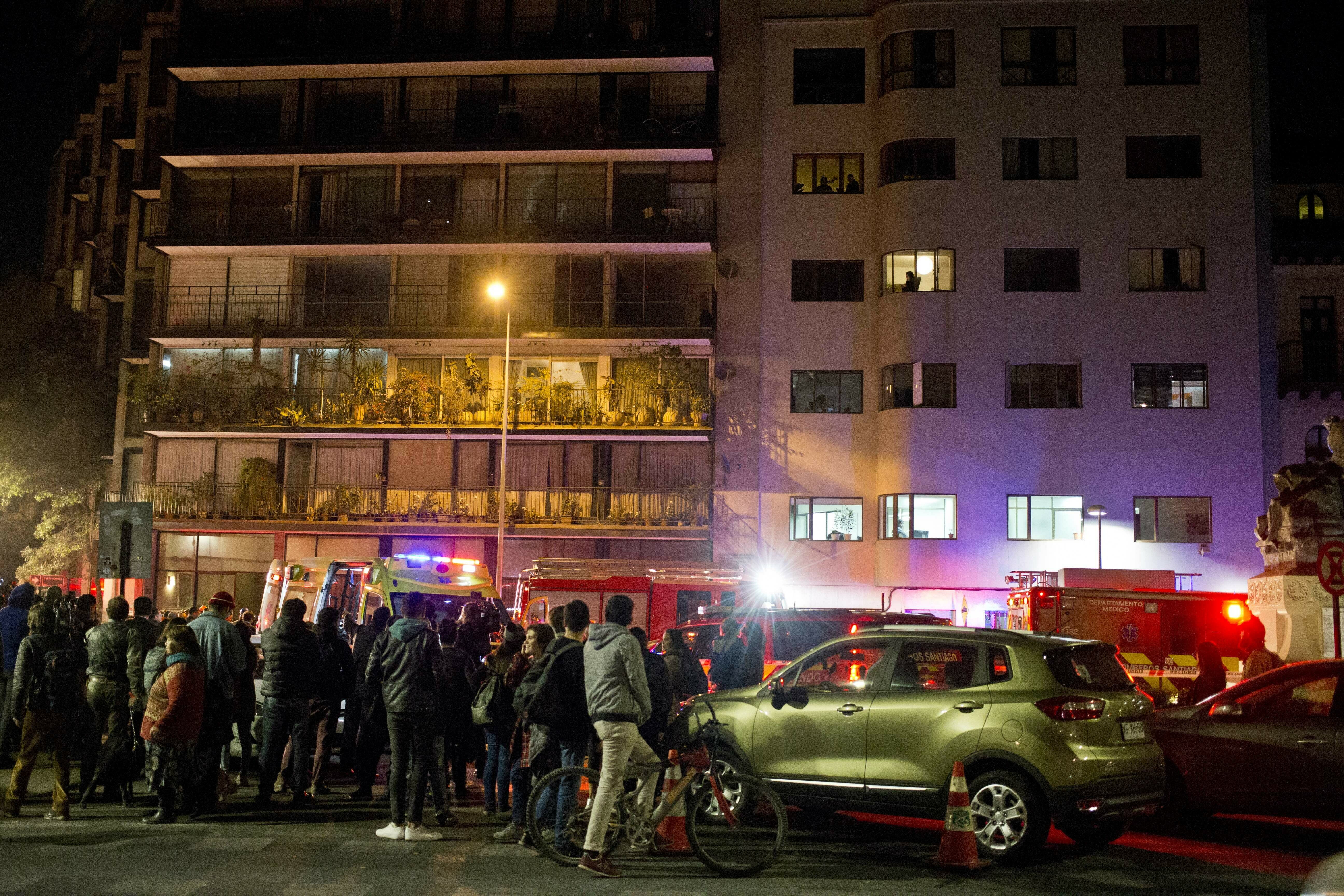 Onlookers look at the building where six Brazilians died in an apartment of apparent carbon monoxide poisoning in Santiago, Chile, Wednesday, May 22, 2019. Police commander Rodrigo Soto said officers found four adults and two children dead at the six-story building. The fire department said a high concentration of carbon monoxide was measured in the apartment, which it said was completely closed. (AP Photo/Esteban Felix)