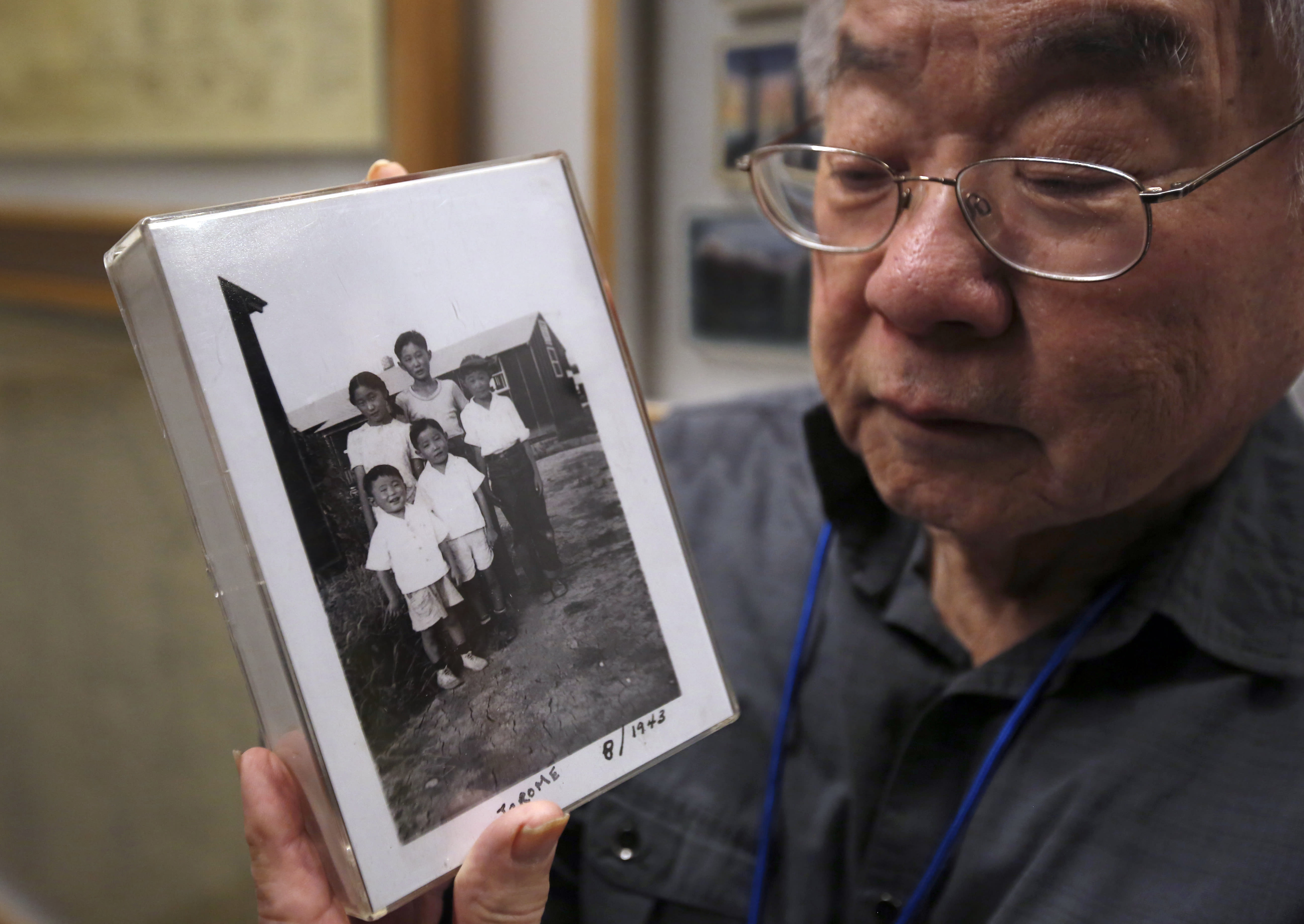 """In this photo taken Tuesday, Feb. 11, 2020, Les Ouchida holds a 1943 photo of himself, front row, center, and his siblings taken at the internment camp his family was moved to, as he poses at the permanent exhibit titled """"UpRooted Japanese Americans in World War II"""" at the California Museum in Sacramento, Calif. Ochida, who is a docent for the exhibit, and his family were forced to move in 1942 from their home near Sacramento to a camp in Jerome, Arkansas. Assemblyman Al Muratsuchi, D-Torrence has introduced a resolution to apologize for the state's role in carrying out the federal government's internment of Japanese-Americans. A similar resolution will be brought up before the state Senate by Sen. Richard Pan, D-Sacramento.(AP Photo/Rich Pedroncelli)"""