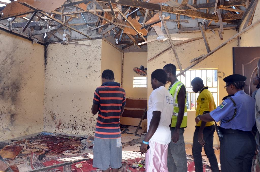 A picture taken on October 23, 2015 in Maiduguri, northeast Nigeria, shows people standing in a mosque following a suicide bombing (AFP Photo/Stringer)