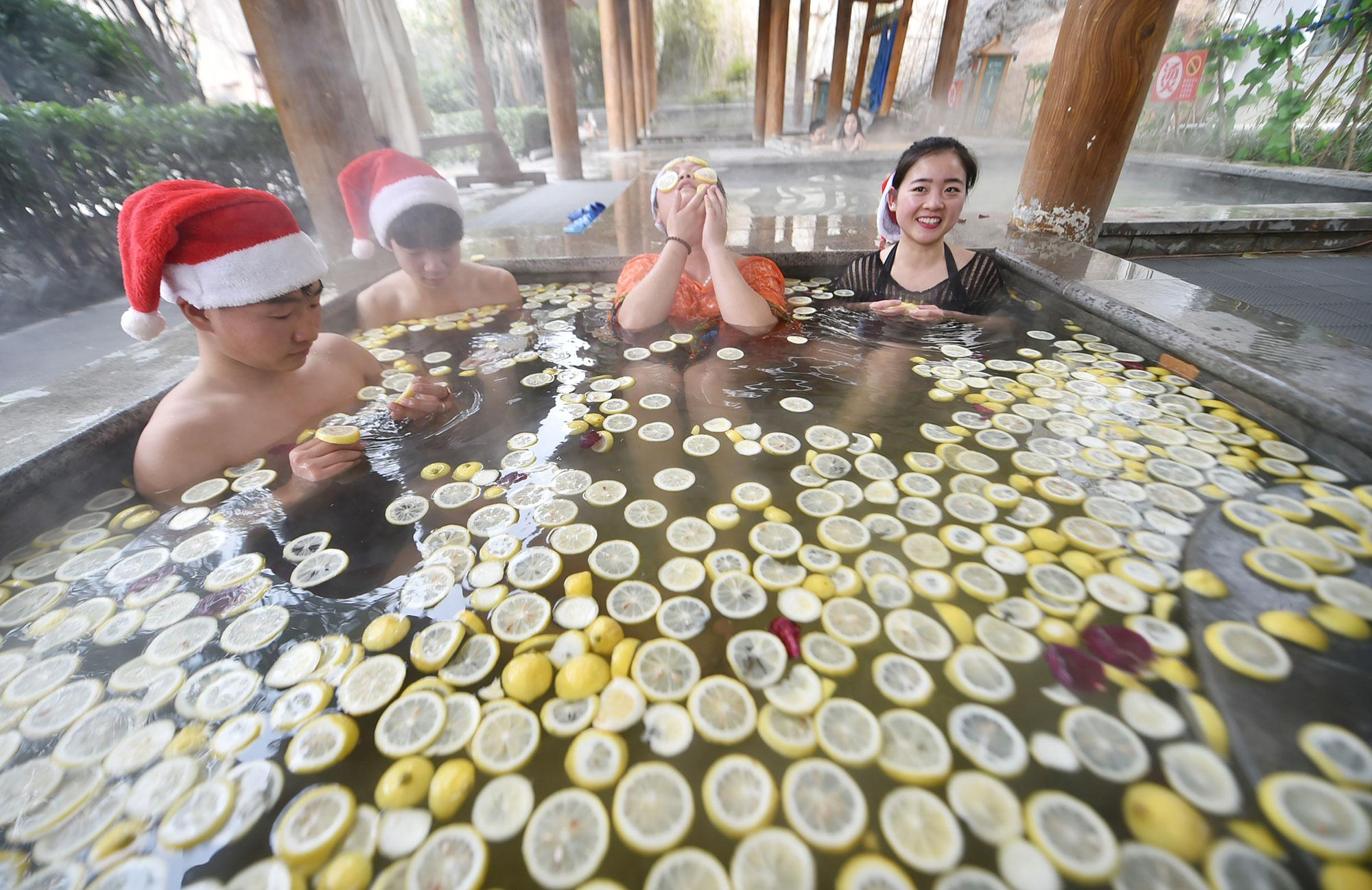 <p>People wearing Santa hats bath with lemon slices at a hot spring center during the Christmas holiday on Dec. 24, 2016 in Luoyang, Henan Province of China. Reportedly taking fruit bath keeps skin in good condition. (Photo: VCG via Getty Images) </p>