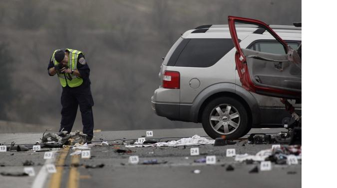 DIAMOND BAR, CALIFORNIA - FEBRUARY 9. 2014: An officer with the California Highway patrol photographs evidence at the wreckage of a car crash on the westbound Pomona Freeway (60) in Diamond Bar on February 9, 2014. A wrong way driver in a Camaro (the very smashed car in front) on the west bound (west of Phillips Ranch Road) crashed head on with a Ford Explorer (middle red SUV) and a Ford Free Style (silver SUV in back). The 21 year old female driver, of Fontana, was charged with felony DUI and manslaughter.  (Photo by Gary Friedman/Los Angeles Times via Getty Images)